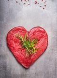 Hårdnar rått kött för hjärtaform med örter och text på grå färger bakgrund arkivfoto