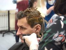 Hårfärgläggning på en man i en skönhetsalong close upp arkivbild