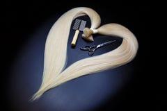 Hårförlängningsutrustning av naturligt blont hår hjärtaform på en mörk bakgrund royaltyfri bild