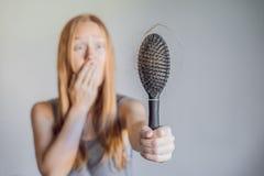 Hårförlust i kvinnabegrepp Mycket borttappat hår på hårkammen arkivbild