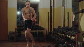 Hårlöst med tatueringar frigör kämpen hoppar med repet i idrottshall 4K lager videofilmer