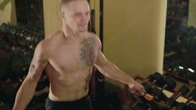Hårlöst med tatueringar frigör kämpen hoppar med repet i idrottshall 4K stock video