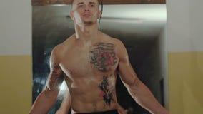 Hårlöst med tatueringar frigör kämpen hoppar med repet i idrottshall långsamt stock video