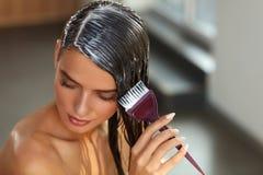 Hårmaskeringar Kvinna som applicerar maskeringen med borsten på vått långt hår royaltyfri foto
