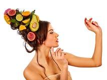 Hårmaskeringen från nya frukter på den kvinnahuvudet och våren blommar Fotografering för Bildbyråer