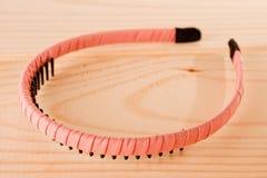 Hårmusikband som slås in med det rosa bandet på träbakgrund royaltyfri foto