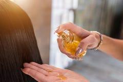 Håromsorg i modern brunnsortsalong frisörkvinnan applicerar en maskering eller en olja på håret av klienten royaltyfri bild