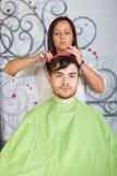 Hårsalong. Frisören gör frisyr för man. royaltyfri bild