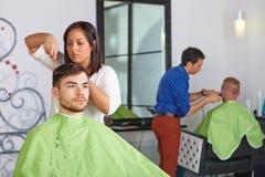 Hårsalong. Frisören gör frisyr för man. royaltyfria foton