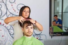 Hårsalong. Frisören gör frisyr för man. royaltyfria bilder