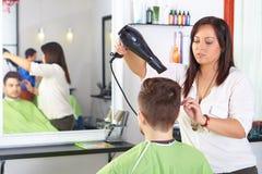 Hårsalong. Frisyr för man` s. Bruk av hårtorken. royaltyfri foto