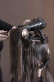 Hårstylist som använder hårtork Fotografering för Bildbyråer
