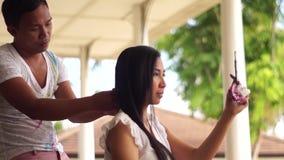 Hårstylist som gör hår till en ung kvinna stock video