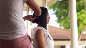 Hårstylist som gör hår till en ung kvinna lager videofilmer