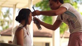 Hårstylist som gör hår till en ung kvinna arkivfilmer