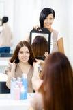 Hårstylist som visar frisyren av klienten i spegel royaltyfri fotografi