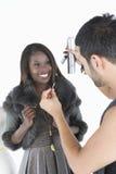 Hårstylisten gör justeringar för att modellera In Fur Jacket Arkivfoto