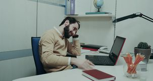 Hårt arbetedag i kontoret, unga män som sitter på hans tabell och ser nervöst till och med bärbara datorn stock video