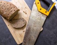 Hårt gammalt bröd och rostig bågfil fotografering för bildbyråer