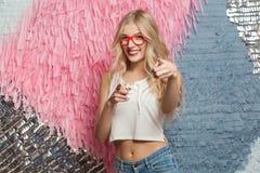 Hé vous ! Fille blonde de bonheur en verres rouges, dirigeant des doigts Photographie stock