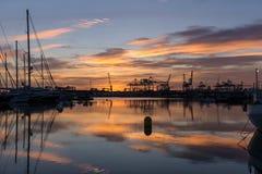 Hébergez les voiliers et les grues de port de cargaison accouplés par crépuscule photo libre de droits