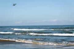 Hélicoptère au-dessus de la mer contre le ciel sans nuages photos libres de droits