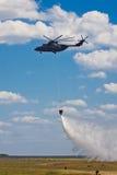 Hélicoptère de lutte contre l'incendie russe avec le waterbag sur la formation extinctrice image libre de droits