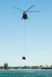 Hélicoptère du mil Mi-17 conduisant une délivrance de l'eau sur Senec Sunny Lakes, Slovaquie photos libres de droits