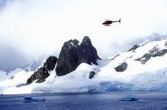 Hélicoptère patrouillant au-dessus des glaciers et des icebergs dans la Manche d'Errera à l'île de Culberville, Antarctique Image stock