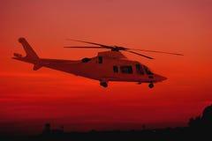 Hélicoptère pendant le coucher du soleil Photos stock
