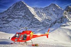 Hélicoptère rouge à la station de sports d'hiver suisse près de la montagne de Jungfrau Photos stock