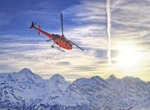 Hélicoptère rouge aux alpes suisses près de la montagne de Jungfrau Photo stock