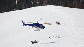 Hélicoptère volant au-dessus de la pente neigeuse de ski Photographie stock