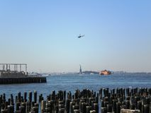 Hélicoptère volant au-dessus de la statue de la liberté Photo libre de droits