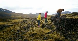 Hélicoptère volant au-dessus du groupe de touristes trimardant sur la montagne Ami marchant dans les domaines de lave en Islande banque de vidéos