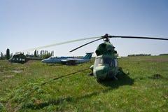 Hélicoptères et avions militaires russes abandonnés sur l'aérodrome abandonné Photographie stock libre de droits