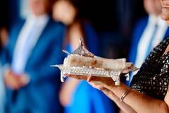 Héritage familial argenté avec des nappes sur un plateau sur les mains des femmes photographie stock