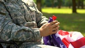Héroe de las fuerzas armadas de arma que sostiene la bandera americana, ceremonia conmemorativa para las víctimas de la guerra almacen de video