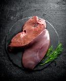 Hígado crudo con eneldo en un tablero de piedra fotos de archivo