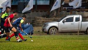 hóquei exterior Jogador de hóquei na ação durante os jogos nacionais de Tailândia fotografia de stock