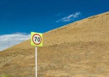 Höchstgeschwindigkeitszeichen mit Verkehr im Hintergrund des blauen Himmels und des gelben Abhangs stockfotografie