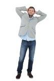 Höflicher Mann in einem Blazer mit den Händen hinter dem Kopf, der Kamera betrachtet Stockbilder