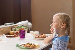 Höfliches kleines Mädchen, das selbst gemachte Pizza isst Lizenzfreie Stockfotos