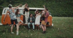 Höften för sommartid, vänner har gyckel i mitt av landskapet med en retro buss arkivfilmer