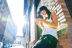 Höftflygturflicka med hörlurar i en stads- miljö Royaltyfri Foto