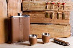 Höftmetallflaska, koppar och kniv på träbakgrund Royaltyfri Bild