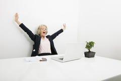 Hög affärskvinna som gäspar, medan se bärbara datorn i regeringsställning Royaltyfria Bilder
