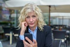Hög affärskvinna som läser ett textmeddelande Arkivfoto