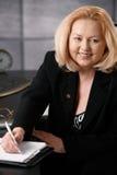 Hög affärskvinna som tar anmärkningen Royaltyfria Bilder