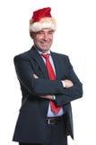 Hög affärsman i den Santa Claus hatten som ler med vikta händer Arkivbilder